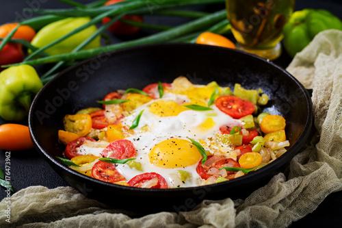 Plakat Smażący jajka z warzywami - shakshuka w smaży niecce na czarnym tle