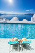 Couple by the swimming pool in Santorini Greece