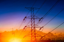 High Voltage Electricity Transmission Pylon Silhouette With Power Plant Against Blue Dusk Sky
