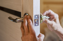Man Repairing The Doorknob. Cl...