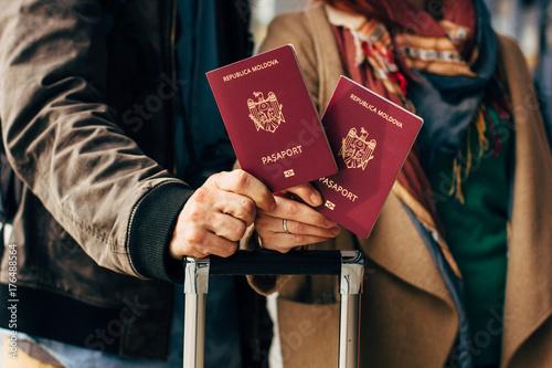 Zdjęcie XXL Para ręka trzyma paszport. Podróżnik z koncepcją bagażu podróży. Turystyka ludzi. Biometryczne paszporty mołdawskie