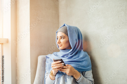 Muslim woman messaging on a mobile phone in cafe