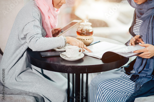 muslim business woman working documents in cafe