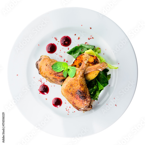 Juicy delicious cooked duck legs served with herbs and sauce in a white plate isolated on black background. Autumn menu in an Italian restaurant. Top view, flat, overhead