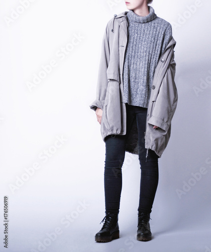 Photo Woman wearing casual outfit with oversized parka jacket, grey knitted turtleneck sweater, black skinny jeans and black biker boots isolated on white background