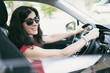 Brunette woman driving car and looking at camera
