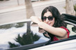 Woman in car roof looing at camera and posing smile