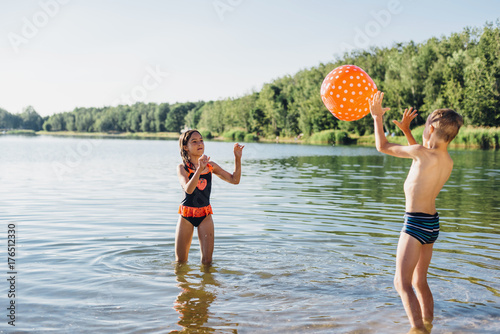 Boy and girl standing at lakeshore playing with beach ball