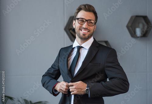 businessman putting on blazer Canvas Print