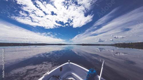 Canvas Print Boot auf spiegelglattem Wasser mit Blick auf blauen Himmel mit weißen Wolken und