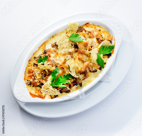 Fototapeta Tasting and appetizing traditional Italian lasagna dish with mushrooms served with fresh dill in a white plate Autumn menu in an Italian restaurant. Hotel service photo background obraz