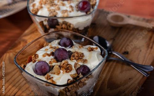 Plakat Jogurt, granola, miód i winogrona zebrane w domu serwowane w szklanej misce