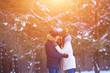 Happy young man and woman hugs in winter forest