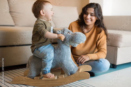 Valokuva Baby playing with a rocking horse