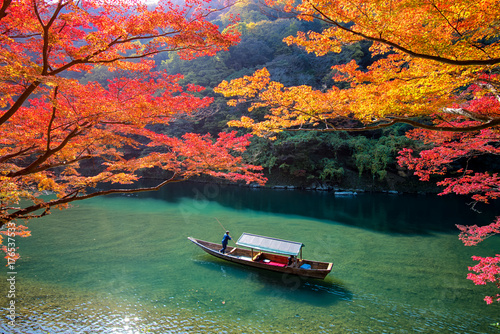 Poster Japan Boatman punting the boat for tourists to enjoy the autumn view along the bank of Hozu river in Arashiyama Kyoto, Japan.