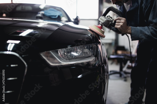 Fototapeta Car detailing - Hands with orbital polisher in auto repair shop. Selective focus. obraz