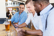 male friends with tablet pc drinking beer at bar