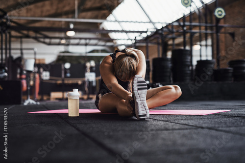 Fényképezés  Fit young woman doing stretches on a gym floor