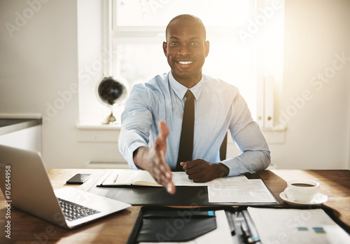 Photo  Smiling young executive sitting at his desk extending a handshak