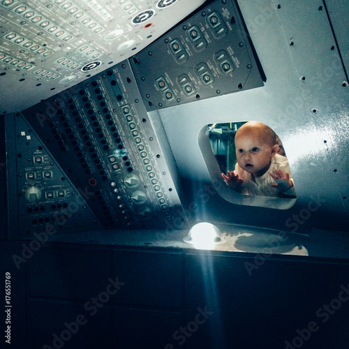 Keuken foto achterwand Nasa A baby looking through the window of an Apollo Space craft replica.