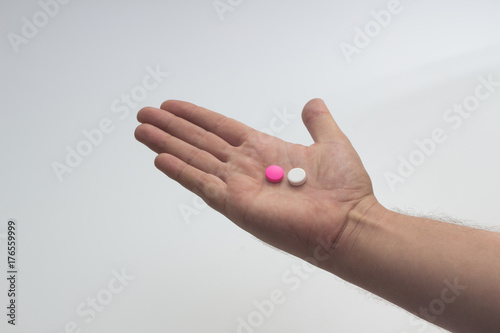 Photo hand holding white and pink pills against white background