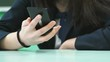 Lesson at school. Unknown student girl in formal suit looking and typing text in black smartphone