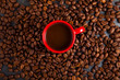 red cup of espresso, coffee with coffee beans around