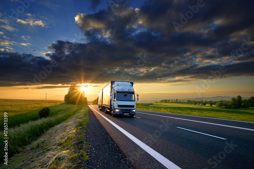 Spoed Foto op Canvas Grijze traf. Small truck driving on the asphalt road in rural landscape at sunset with dark clouds