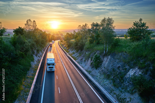 Zdjęcie XXL Trzy ciężarówki jedzie na autostradzie w wiejskim krajobrazie przy zmierzchem. Widok z góry.