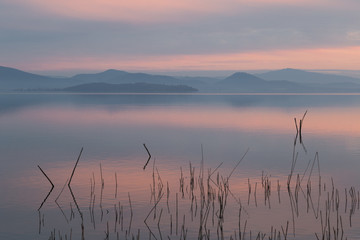 Fototapeta Minimalistyczny A lake at dusk, with beautiful, warm tones in the sky and water reflections, distant mountains and hills, branches in the foreground