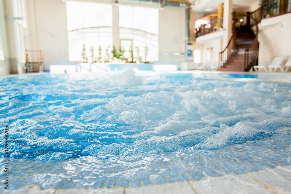 Fototapeta Waves and splashes in warm spa jacuzzi with nobody around