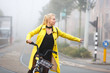 Young woman with bicycle in a misty city