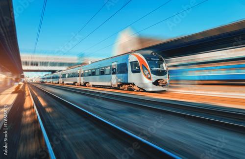 Zdjęcie XXL Wysoki prędkość pociąg w ruchu przy stacją kolejową przy zmierzchem w Europa. Nowoczesny pociąg intercity na peronie kolejowym z efektem rozmycia w ruchu. Przemysłowa scena z poruszającym pociągiem pasażerskim na linii kolejowej