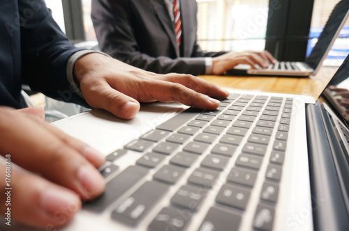 Fototapety, obrazy: Man working by using a laptop computer on wooden table. Hands typing on a keyboard