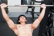 young man execute exercise with weightlifting machine in fitness center. male athlete pump up muscle in gym. sporty guy working out in health club.