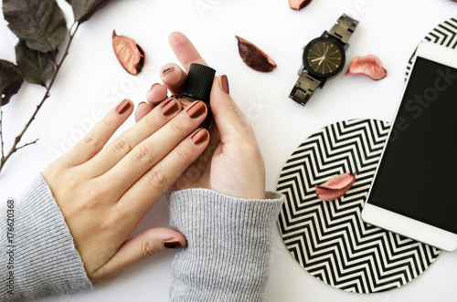 Female hands with nail polish on white background with mobile phone, watch and autumn petals Canvas Print