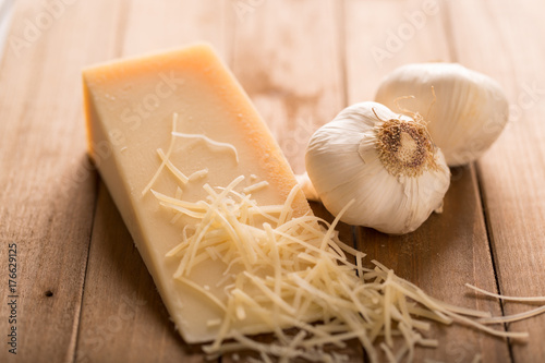 Parmesan and Garlic Close Up. an close up view of a wedge of parmesan cheese and two cloves of garlic on wood with shredded cheese