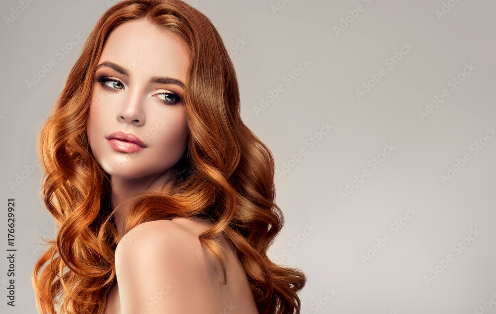 Fototapeta Beautiful model girl with long red curly hair .Red head . Care and beauty hair products