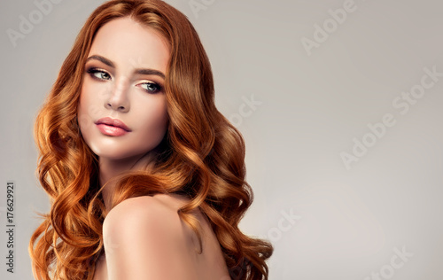 Obraz Beautiful model girl with long red curly hair .Red head . Care and beauty hair products   - fototapety do salonu