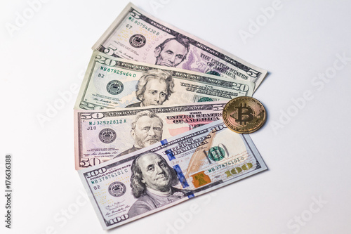 Photo  Four banknotes of US dollars and gold bitcoin on them.