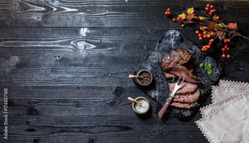 Staande foto Vlees Sliced grilled roast beef with salt and pepper on marble plate on wooden old rustic table Black background.