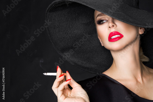 Fotografie, Obraz  Elegant woman, femme fatale in black hat with cigarette in hand