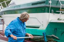 Caucasian Man Scrubbing Boat W...