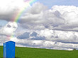 blue portable bathroom with rainbow on green hill with sky and cloud horizon