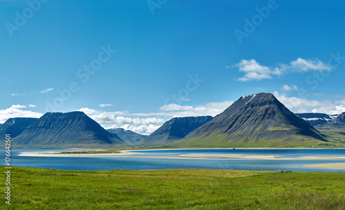 Deurstickers Noord Europa Travel to Iceland. beautiful sunrise over the ocean and fjord in Iceland. Icelandic landscape with mountains, blue sky and green grass on the foreground. View of Flateyri, a village in the north-west