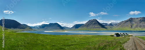 Garden Poster Blue jeans Travel to Iceland. beautiful sunrise over the ocean and fjord in Iceland. Icelandic landscape with mountains, blue sky and green grass on the foreground. View of the road to houses in the north-west