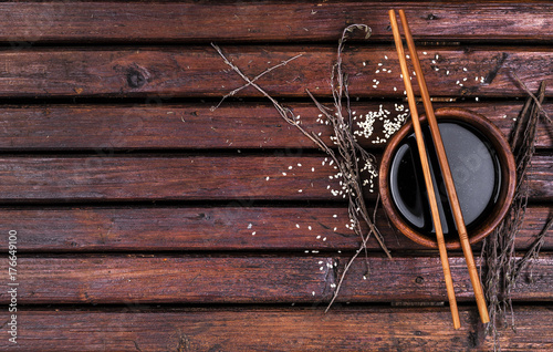 Soy sauce and chopsticks on a wooden table top view