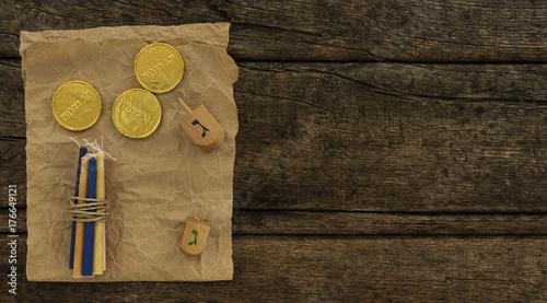 Zdjęcie XXL Chanuka dreidels z niektóre Hanukkah świeczkami i Hanukkah monetami na rocznika drewnianym tle z kopii przestrzenią. Transkrypcja tekstu hebrajskiego: litera G i Wesołych Świąt