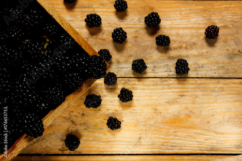 Fényképezés  Ripe blackberries in a basket on a rustic wooden table.