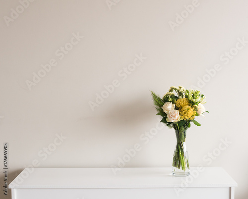 Fényképezés  Yellow and cream flowers in glass vase on white sideboard against neutral wall b